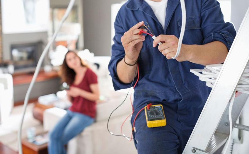 Электрик проверяет мультиметром провод