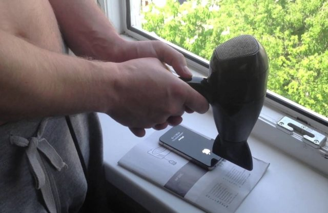 Мужчина сушит смартфон феном
