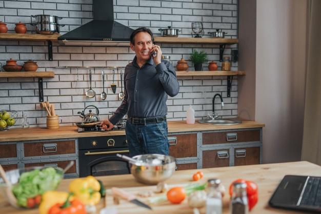 Мужчина на кухне говорит по телефону