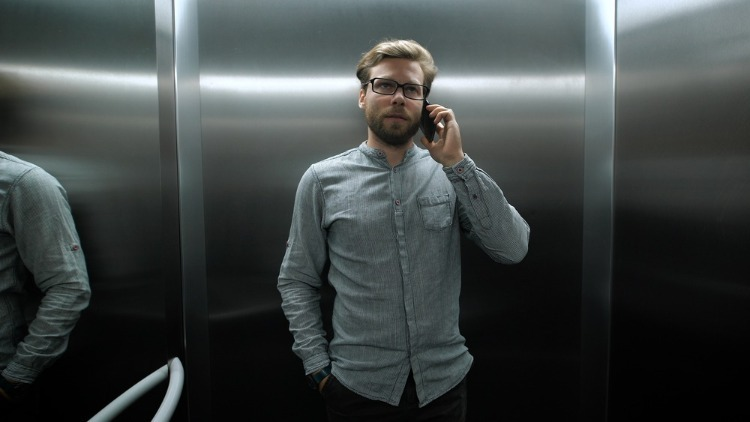 Мужчина в лифте говорит по телефону