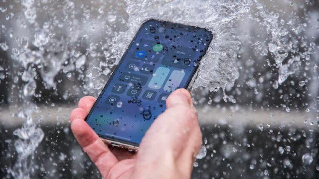 Смартфон в руке под струей воды