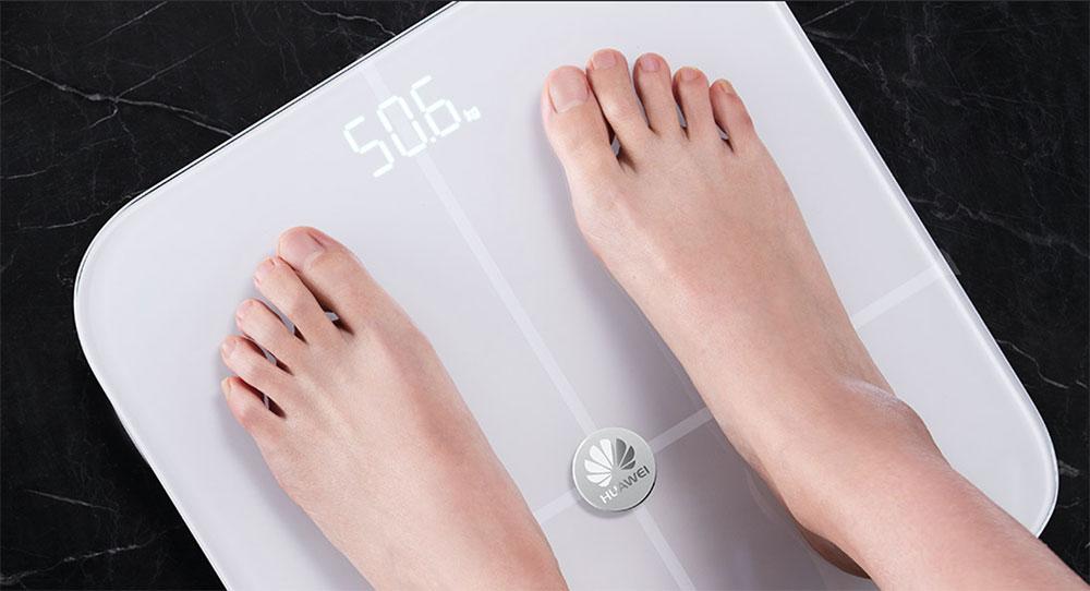 Напольные весы и человек сверху