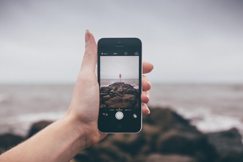 Смартфон в руке на фоне моря