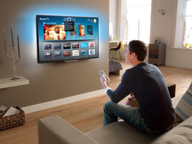 Мужчина настраивает телевизор
