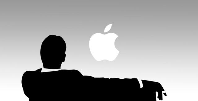 Человек в костюме на фоне логотипа Apple