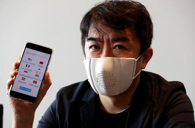 Человек в маске держит смартфон