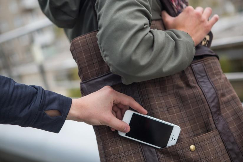 Человек вытягивает смартфон из кармана другого