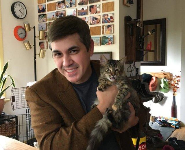 Мужчина держит кота на руках