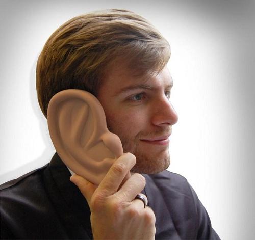 Мужчина держит возле уха смартфон в чехле с уха