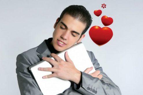 Парень обнимает ноутбук