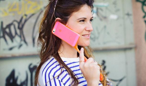 Девушка держит смартфон за ручку чехла