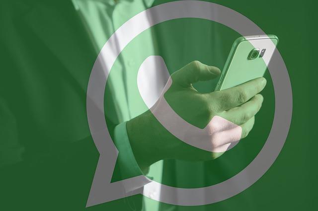 Логотип WhatsApp на фоне смартфона в руке