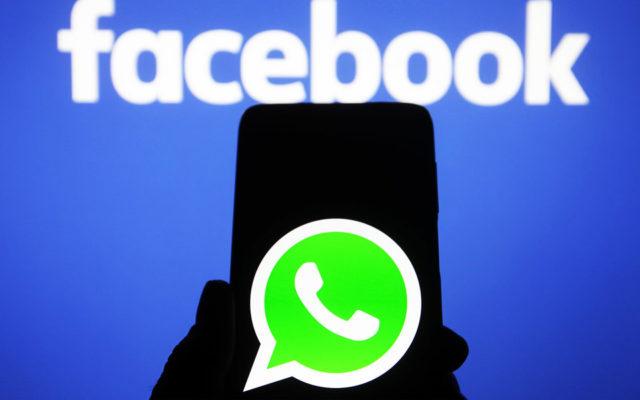 WhatsApp на рабочем столе смартфона на фоне вывески Facebook