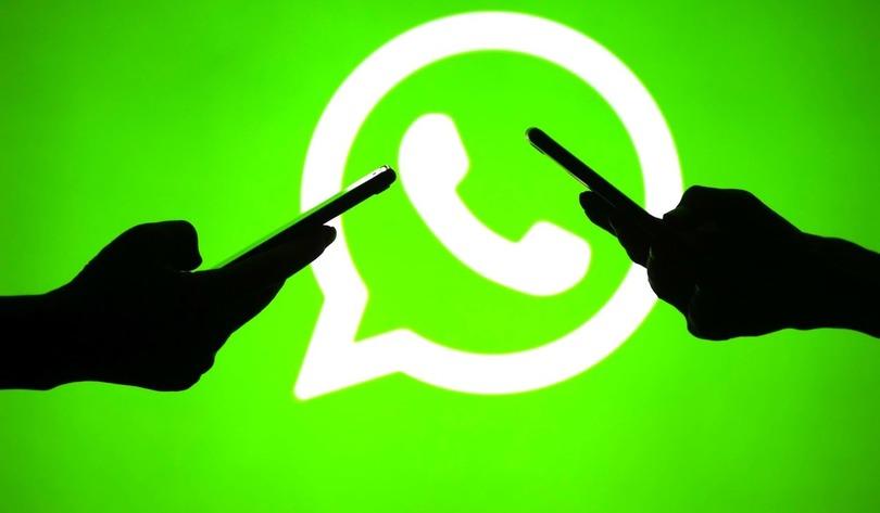 Смартфоны в руках на фоне логотипа WhatsApp