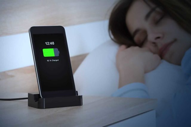 Смартфон на зарядке на фоне спящей в кровати девушки