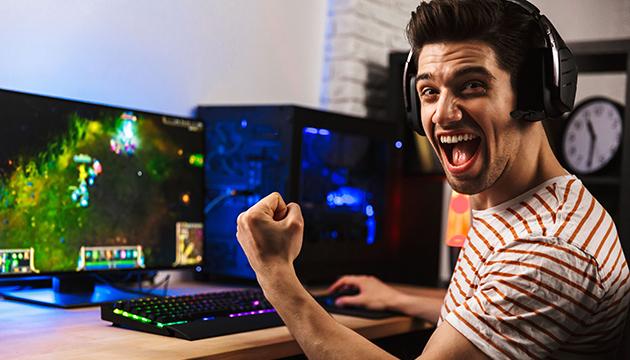 Радующийся победе геймер за ПК