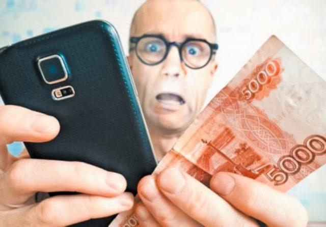 Испуганный мужчина со смартфоном и деньгами в руках