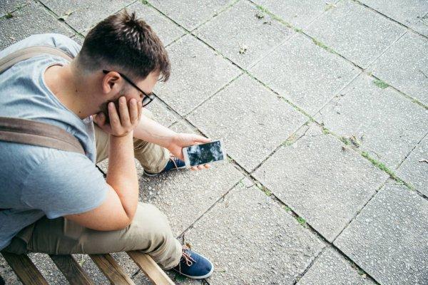 Парень подперев щеку сидит на лавочке и держит в руках разбитый смартфон