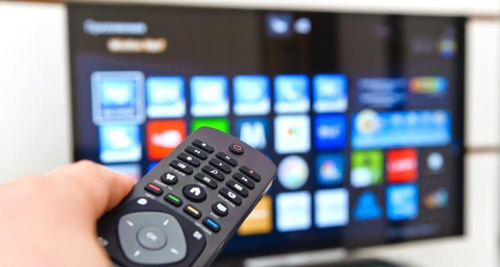 Пульт ДУ в руках на фоне TV-панели