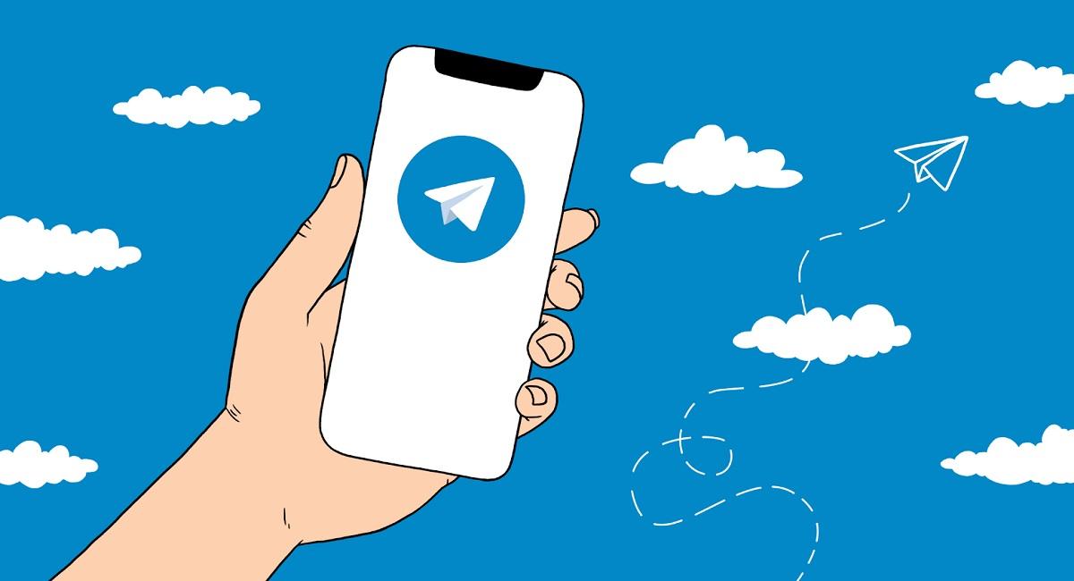 Рисунок — смартфон в руке с логотипом Telegram и парящий бумажный самолетик на заднем плане