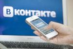 Смартфон в руке на фоне логотипа Вконтакте