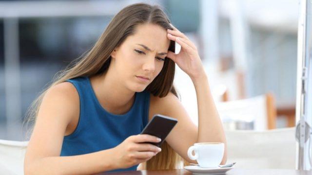 Нахмуренная девушка смотрит в смартфон