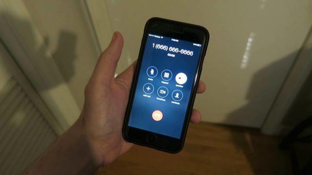Смартфон в руке со странным номером на экране вызова