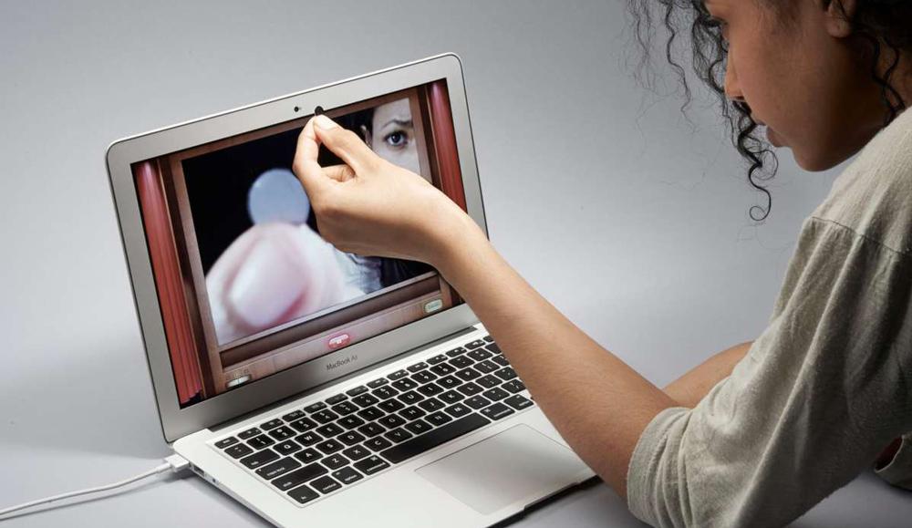 Девушка заклеивает камеру ноутбука