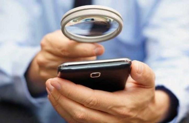 Пользователь рассматривает смартфон в лупу