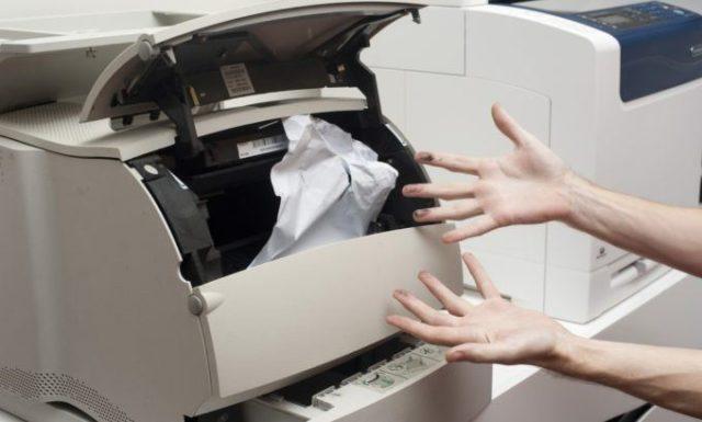 Протянутые руки к жующему бумагу принтеру