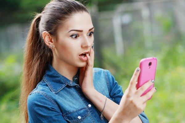Девушка удивленно смотрит на экран своего смартфона