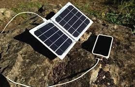 Солнечная батарея и подключенный к ней смартфон на земле
