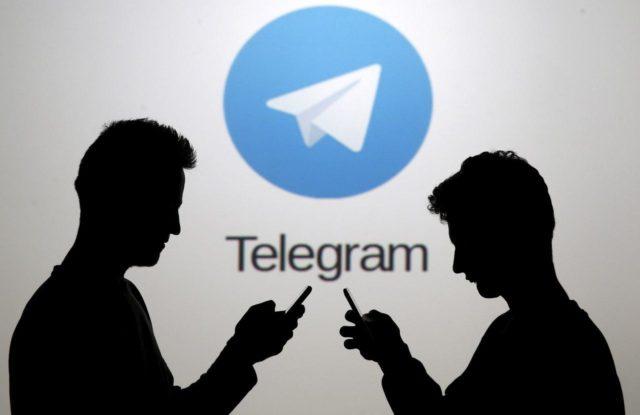 Две темные фигуры на фоне логотипа Telegram