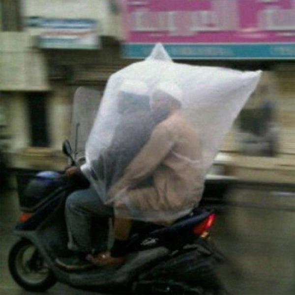Водитель и пассажир под кульком от дождя на мопеде
