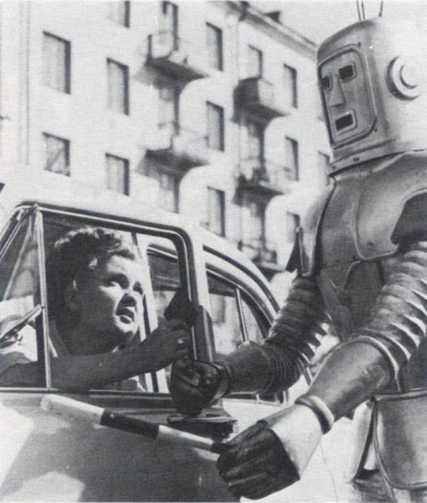 Советский роботизированный регулировщик и дама за рулем, предъявляющая водительское удостоверение