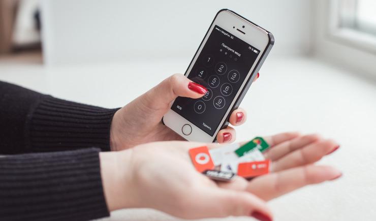Смартфон в руке и SIM-карты