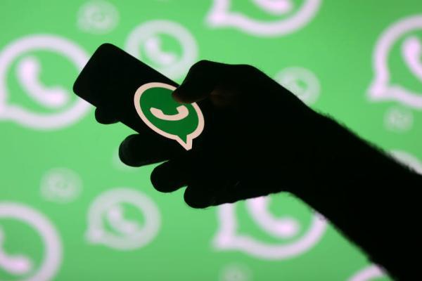 Смартфон со значком WhatsApp в руке