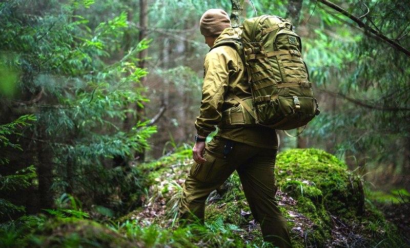 Человек в камуфляже с рюкзаком в лесу