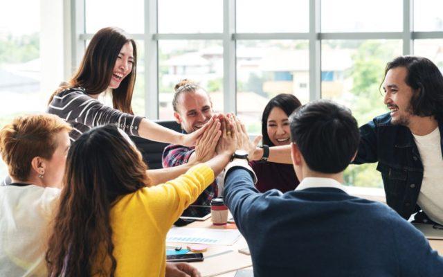 Компания молодых людей в офисе смеются и соединяют вместе ладони