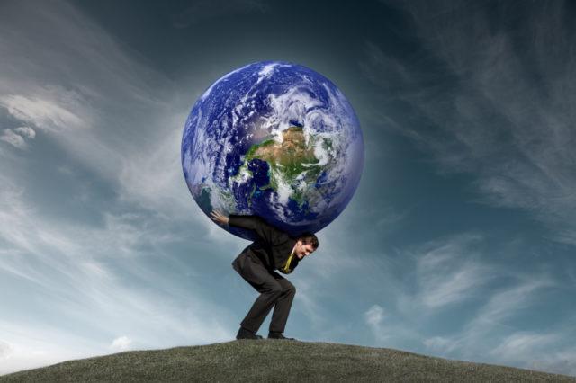 Мужчина в костюме на холме держит на своих плечах земной шар