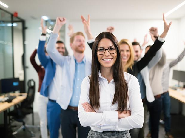 Девушка на переднем плане ликующего коллектива в офисе