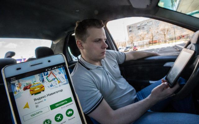Водитель за рулем смотрит в навигатор на планшетном ПК