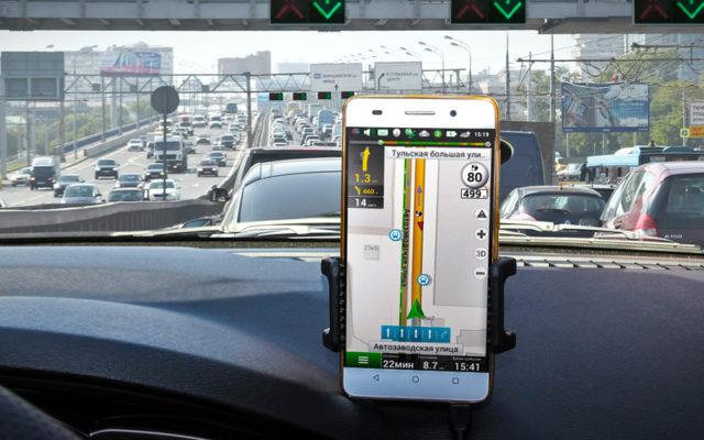 Приложение Яндекс.Навигатор в смартфоне, установленном на автомобильном торпедо