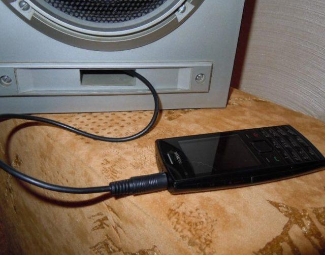 Телефон, подключенный к старой колонке