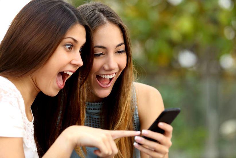 Девушки со смартфоном смеются