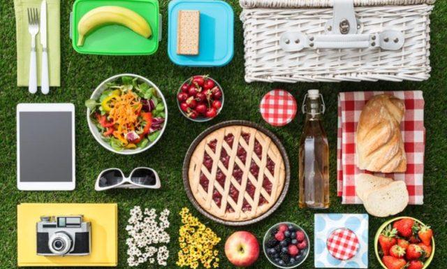 Различные продукты для пикника, упорядоченно разложенные на траве