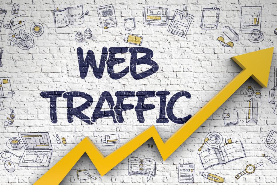 Надпись Web Traffic на кирпичной стене и желтая стрелка вверх