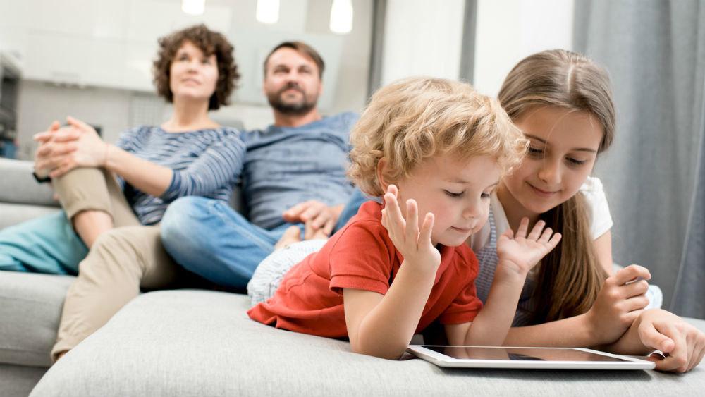 Дети смотрят в планшет, пока родители заняты своими делами