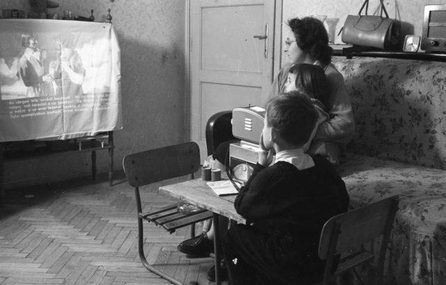 Женщина и дети смотрят диафильм на скатерти вместо экрана