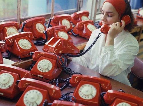 Девушка говорит по телефону в окружении множества телефонных аппаратов